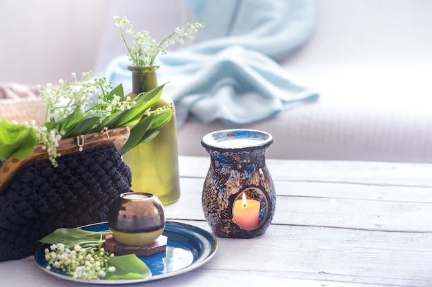 Beautiful burning candles with green leaves in purse on white table