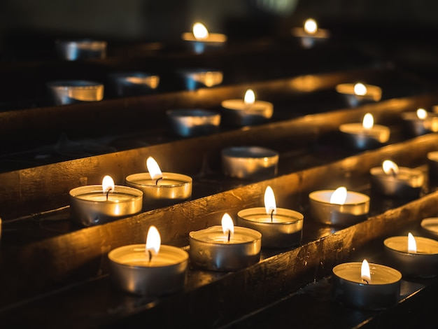 오래된 교회의 어둠 속에서 아름답고 불타는 축제 양초