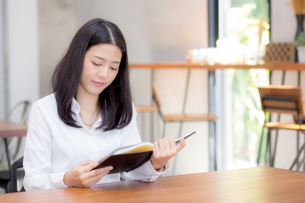 Beautiful business asian woman reading on notebook on table