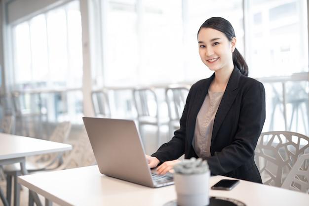 복사 공간 busi가 있는 컴퓨터를 사용하여 사무실 책상에서 일하는 양복을 입은 아름다운 비즈니스 아시아 여성