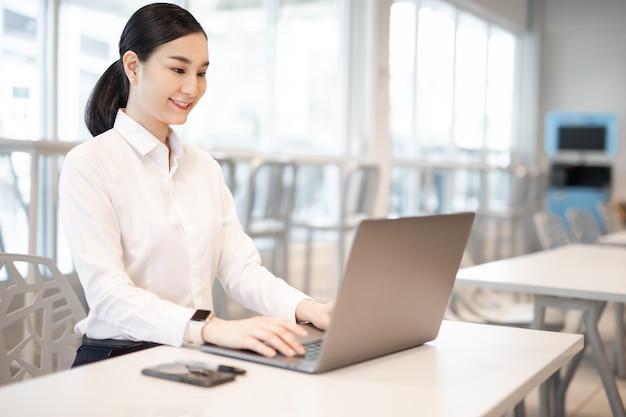 복사 공간이 있는 컴퓨터를 사용하여 사무실 책상에서 작업하는 정장을 입은 아름다운 비즈니스 아시아 여성 프리미엄 사진