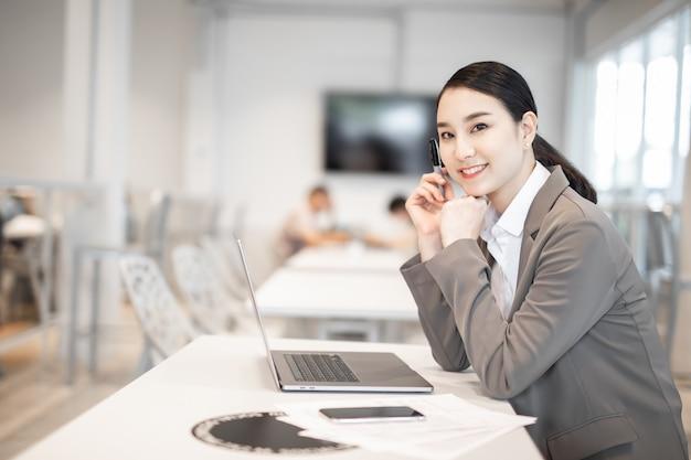 복사 공간이 있는 컴퓨터를 사용하여 사무실 책상에서 작업하는 정장을 입은 아름다운 비즈니스 아시아 여성