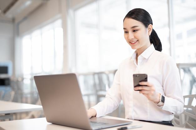 스마트 폰으로 컴퓨터를 사용하여 사무실 책상에서 일하는 정장을 입은 아름다운 비즈니스 아시아 여성
