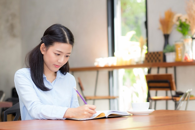 Beautiful business asian young woman writing on notebook on table.