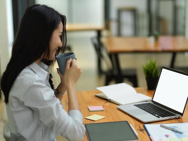 아름다운 비즈니스 직원 여성은 사무실에서 노트북을 통해 업무를 보는 동안 커피를 마신다