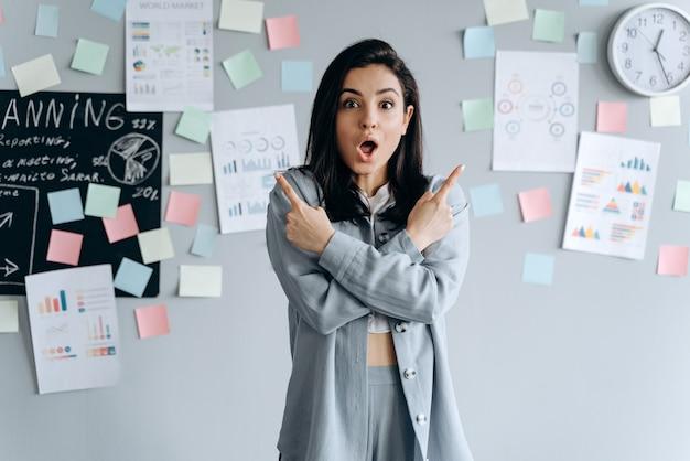회색 벽에 아름다운 비즈니스 소녀가 검지 손가락을 보여주고 팔을 넘어