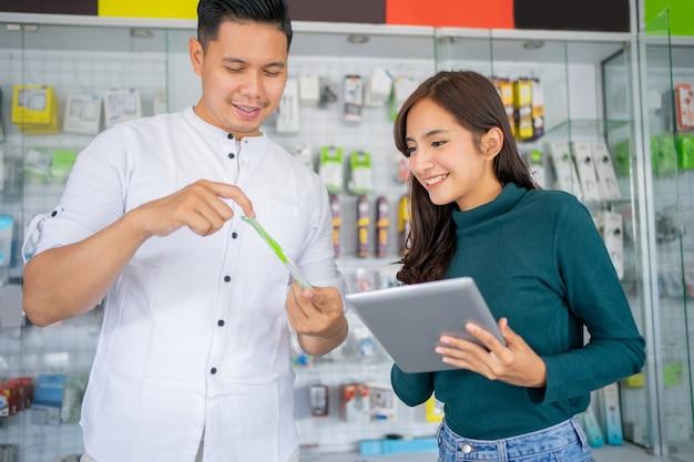 男性の店員とアクセサリー製品の在庫をチェックするタブレットを使用している美しいビジネスガール...