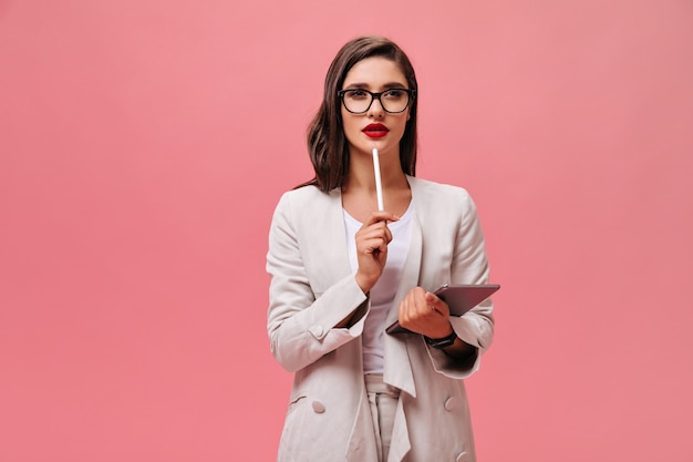 Beautiful business lady in eyeglasses and modern suit thoughtfully posing with computer tablet on isolated pink background.