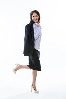 아름다운 비즈니스 여성이 흥미롭고 웃고 있는 모습으로 서 있습니다.