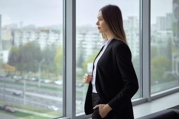 窓際に思慮深く立っている美しいビジネスレディ