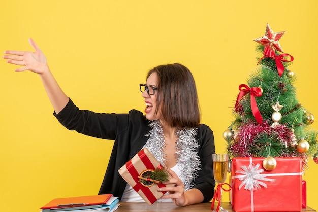 Bella signora di affari in vestito con gli occhiali che tiene il suo regalo e chiama qualcuno seduto a un tavolo con un albero di natale su di esso in ufficio