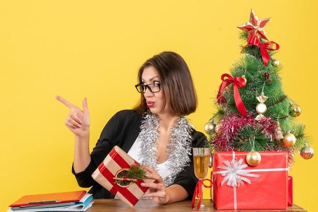 Bella signora di affari in vestito con gli occhiali che indica qualcosa seduto a un tavolo con un albero di natale su di esso in ufficio