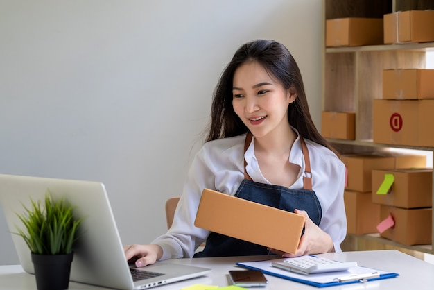 エプロンを着た美しいビジネスオーナーのアジア人が、自宅でノートパソコンを使って顧客に配達するための小包箱を準備しています。