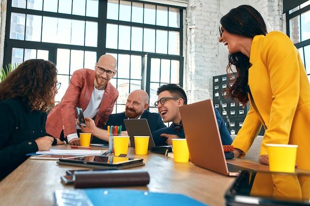Красивые деловые люди используют гаджеты, разговаривают и улыбаются во время конференции в офисе выборочный фокус
