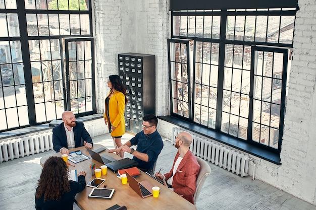 아름다운 비즈니스 사람들은 가제트를 사용하여 사무실에서 회의 중에 이야기하고 웃고 있습니다.