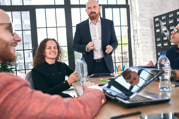 美しいビジネスマンは、オフィスでの会議中にガジェットを使用し、話したり、笑ったりしています。