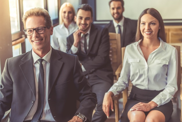 Beautiful business people in formal clothes are smiling
