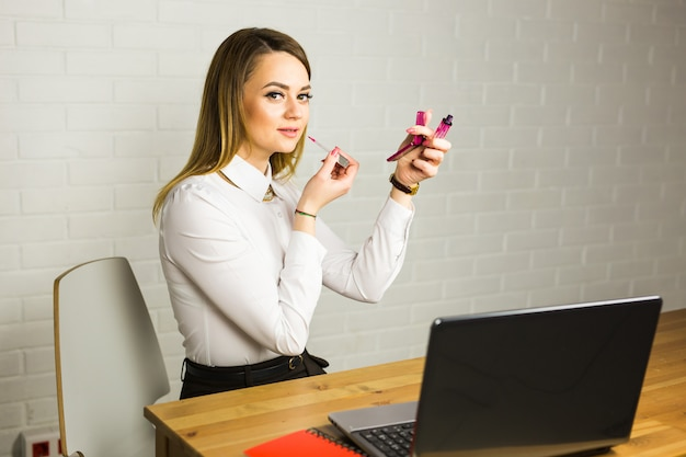 Beautiful business woman applying makeup in office