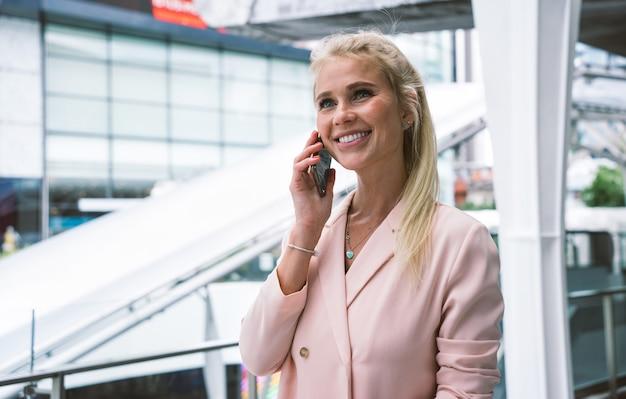 작업 여행을 떠나 공항에서 아름 다운 비즈니스 우먼. 스마트폰을 사용하여 전화 걸기