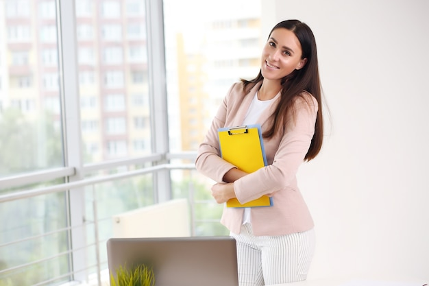Beautiful business woman on the background of the modern office.