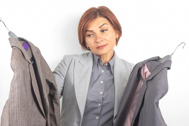 Красивая деловая женщина выбирает офисную одежду из разных курток. мода и красота в одежде.