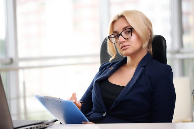 그녀의 사무실에서 컴퓨터에서 작업하는 동안 꿈꾸는 아름다운 비즈니스 우먼