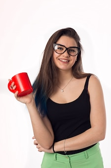 Beautiful business woman drinking coffee tea from a red cup. portrait. office worker.