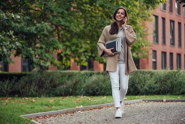 노트북과 노트북 야외에서 캐주얼 복장을 한 아름다운 비즈니스 여성이 스마트폰으로 말합니다