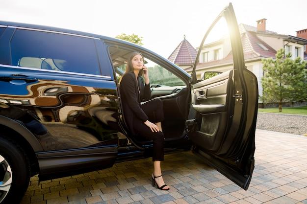 Красивая деловая женщина в темном костюме использует смартфон и улыбается, сидя на пассажирском сидении в роскошном черном автомобиле