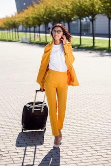 Красивая деловая женщина в стильном желтом костюме тянет чемодан, спешит в аэропорт и разговаривает по смартфону. привлекательная молодая женщина собирается в командировку, потянув ее чемодан за ней.