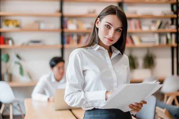 作業論文と近代的な会社のオフィスで美しいビジネス女性
