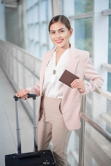 Beautiful business woman is walking in airport, business travel concept
