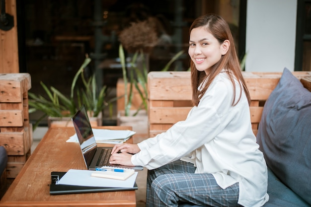 Beautiful business woman is working with her laptop computer in coffee shop