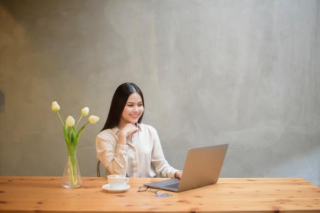 美しいビジネス女性はコーヒーショップでノートパソコンを使用しています。