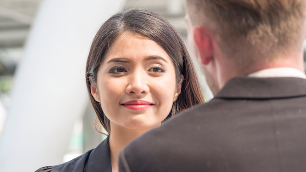 美しいビジネス女性は、幸せな笑顔で話す他の人の話を聞く。