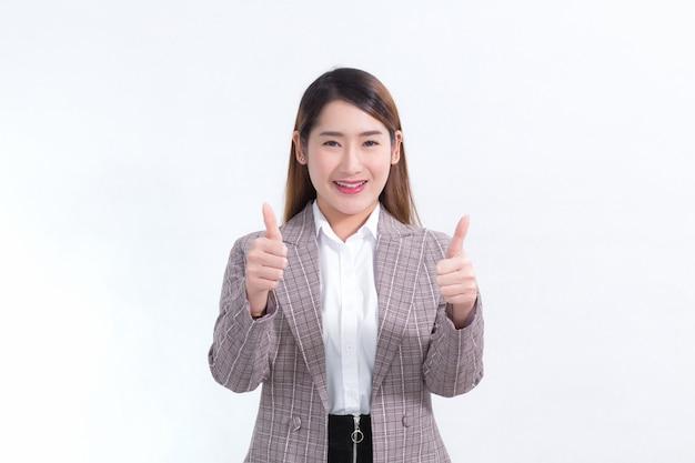 Красивая деловая женщина с длинными волосами, азиатка в костюме улыбается, показывает палец вверх и что-то представляет