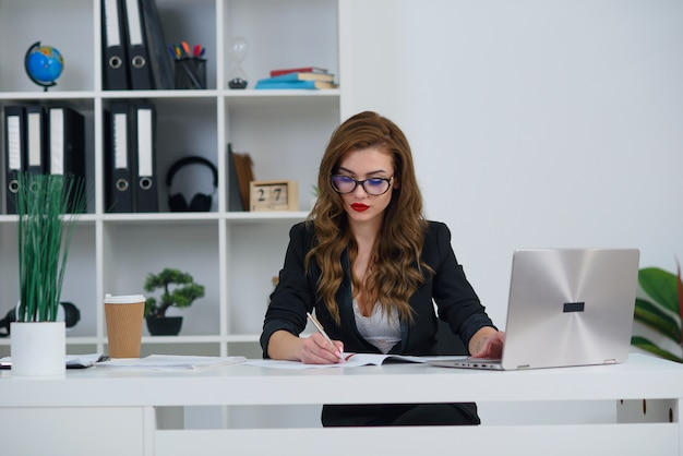 Beautiful business woman in office wearing stylish clothes, makes some notes on paper while sitting at modern cozy office.
