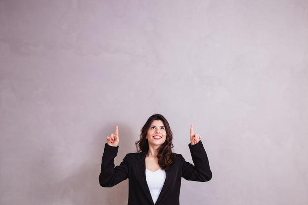 Beautiful business woman pointing up with space for text.