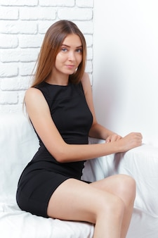 Beautiful business woman sits on sofa