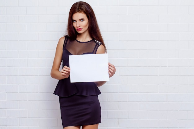 A beautiful business woman standing in a black dress in the studio and holding up a empty white sign