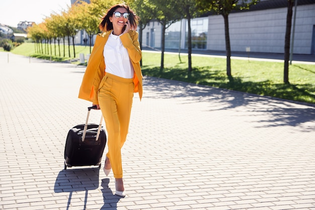 Beautiful business woman in stylish yellow suit pulls a suitcase, hurries to the airport and talks on smartphone. attractive young woman going on a business trip pulling her suitcase behind her.