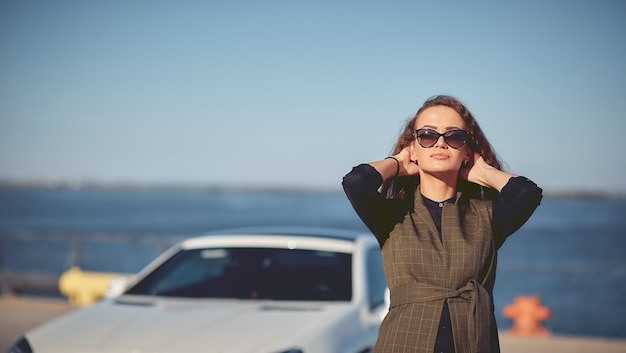 Beautiful business woman in sunglasses and business suit at sunset on the background