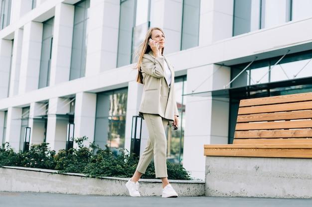Красивая деловая женщина разговаривает по телефону и гуляет по улице города