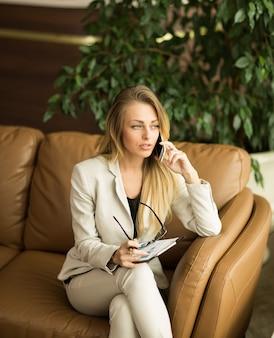 아름 다운 비즈니스 우먼입니다. 계약에 관한 전화 통화.