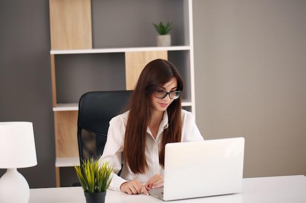 사무실에서 작업하는 동안 아름 다운 비즈니스 우먼 노트북과 미소를 사용합니다.