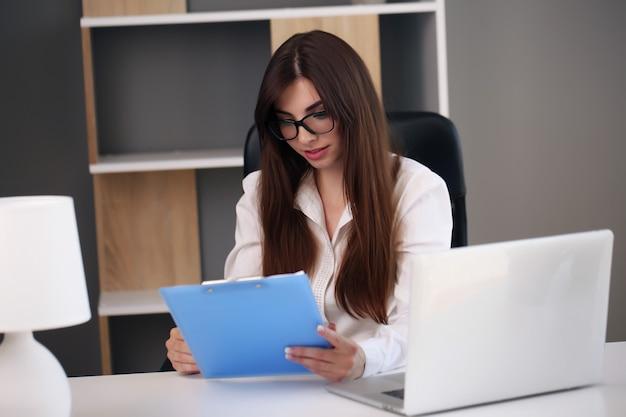 사무실에서 작업하는 동안 아름 다운 비즈니스 여자 노트북과 미소를 사용