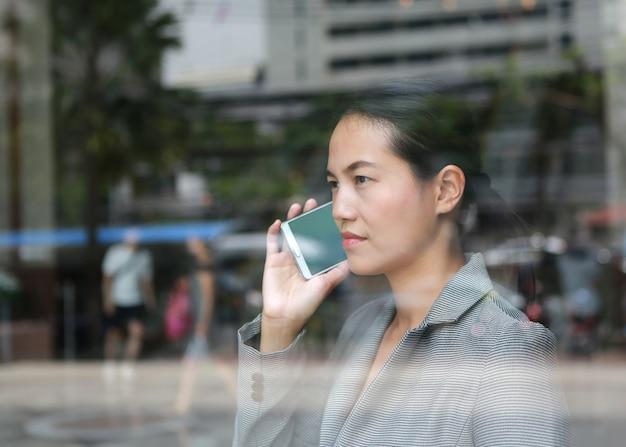 オフィスビルの反射ガラスでスマートフォンを使用している美しいビジネス女性。