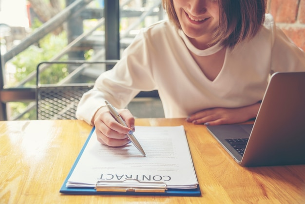 プロジェクトを開始する新しい契約に署名するペンを使用して美しいビジネス女性。働く女性は屋外で働きます。ビジネスの概念。
