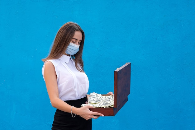 Beautiful business woman wearing a medical mask due to a coronavirus infection and holding dollars for her safety