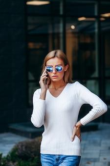 メガネと通りの背景に電話の美しいビジネス女性